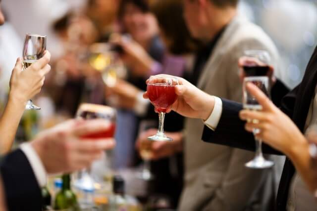 אנשים מחזיקים כוסות יין באירוע בניין אירועים