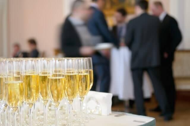 כוסות שמפניה ועובדים משוחחים באירוע עסקי בניין אירועים